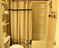 Decorative shower curtains are so expensive, make your own with painters drop cloth and sew on some fabric, ribbon and add grommets.