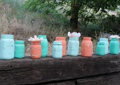 Super cute! Shades of aqua, and coral painted Mason jars, chipped for that gorgeous vintage touch. Would be great as a centerpiece with white flowers at a wedding or other event! Would be SO easy to DIY!