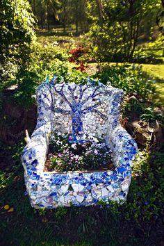 A blue and white mosaic garden seat/planter.   En gammal fåtölj har Anette byggt om med cement och torv och sedan klätt med massor av sönderslaget porslin, speglar och loppisfåglar.Foto Göran Stenberg