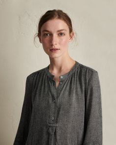 Long collarless shirt dress in a lightweight, Italian-woven, gauzy wool blend. Long sleeves with panel detail and gathers at cuff. Box pleat below button placket. Curved, split hem. Corozo buttons. Pockets. Viscose slip.