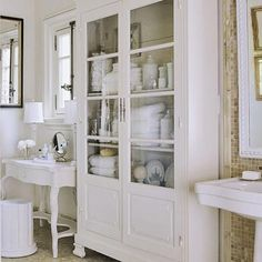 Love this storage cabinet with the glass doors for a bathroom