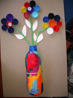 Cute flower project. Use a plastic bottle for the vase and bottle caps for the…
