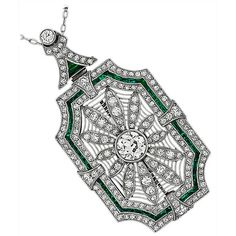 "Art Deco Emerald Diamond Platinum Pin/Pendant Necklace. This stunning pin centers a sparkling old mine cut diamond weighing approx. 1.15 carat. The color of the diamond is H-I with VS1 clarity. It has amazing open work with milgrain throughout and is set with small old mine cut diamonds weighing approximately 5 carat. The diamonds are flanked by bright green french cut emerald accents. The pin can also be worn as a pendant and comes with a 17"" long platinum chain that is adorned with pearls."