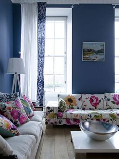 Blue walls, long floaty curtains and floral-printed sofa. I'm not usually a big fan of the flowers-on-fabric look, but this room is WORKING it.