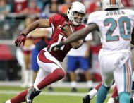 Arizona Cardinals wide receiver Larry Fitzgerald (11) scores a touchdown as Miami Dolphins free safety Reshad Jones (20) defends during the second half of an NFL football game, Sunday, Sept. 30, 2012, in Glendale, Ariz. (AP Photo/Paul Connors)