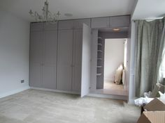 Wardrobe doors reveal hidden dressing room containing additional wardrobe units (image 2 of 3)