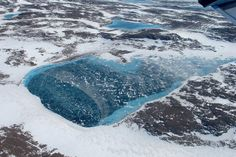 Greenland in White, Brown, and Blue: Meltwater accumulates in the rocky terrain near the northeastern coast.