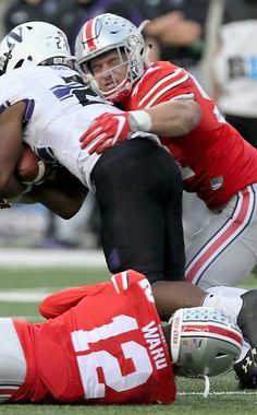 Ohio State Buckeyes defensive end Nick Bosa (97) and cornerback Denzel Ward (12) combine to tackle Northwestern Wildcats running back Justin Jackson (21) in the third quarter,