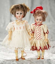 """Two miniature German bisque flapper girls in antique costumes by Simon and Halbig~~7"""" (18 cm.) and 8"""". Each has bisque socket head, blue sleep eyes, painted features, open mouth, four teeth, brunette mohair bobbed wig, five piece flapper style body, slender limbs, painted shoes and socks. Marks: S&H 1078 Germany. Generally excellent. Simon and Halbig, circa 1917, the dolls have original wigs, bodies, body finish, wonderful antique costumes."""