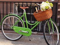 Hermosa bici en color verde y canasta de mimbre.