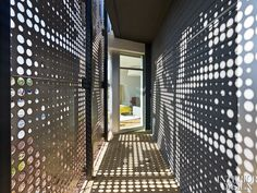 Blitz: Laser-cut perforations punctuate the custom steel screens wrapping the showroom.