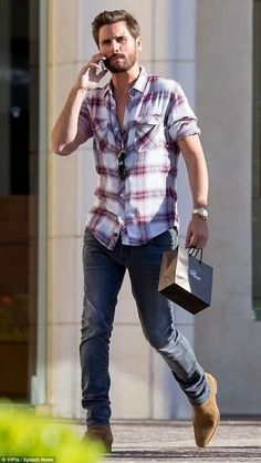 Scott Disick wearing White and Red Plaid Long Sleeve Shirt, Navy Jeans, Tan…