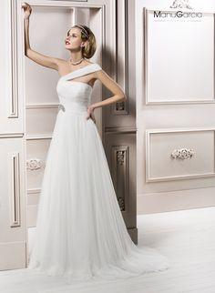Vestido de novia en tul de seda natural con falda vaporosa en diferentes capas,cuerpo drapeado con banda asimétrica desde el hombro recogida en la cintura con un broche de cristal.