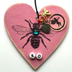 Bee Mine Wood Heart Ornament.  The wood heart is painted and distressed with acrylic paint.  The bee is stamped on the heart with permanent black ink and embellished with one of our new 2015 Cupid stamps and letter beads.