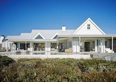 Exterior de una casa en la playa de Sudáfrica con piscina, hamaca 'Kai pod' y techo de chapa con terminación plata que refleja el calor del sol y reduce el consumo energético.