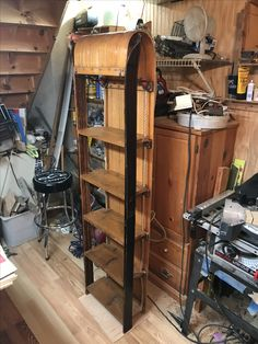 An old toboggan upcycled into a bookshelf with a pair of vintage wooden skis and some old cedar barn wood for shelves.