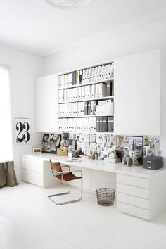 Modern and minimal home office with organized shelves and collaged artwork