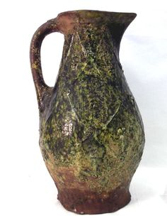 London-type ware. Pottery jug; pear-shaped in the highly decorated style; green glaze; lipped rim & rod handle; applied relief lattice pattern with ring-and-dots, strip and pellet; overlapping pads on stems in each lozenge.