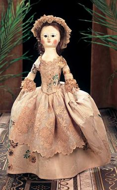 Early English Wooden Doll with Two Black Beauty Spots,wearing lace-front gown of antique embroidered silks with lace trim,lace cap,antique undergarments including rare pannier hoop that is likely original. 18th century