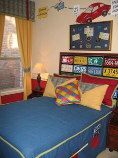 A fun car theme; a road map painted on the wall, old license plates on the headboard and bright race-inspired checkered pillows.