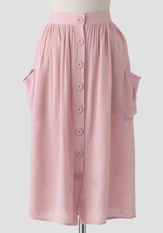 Complete with two side pockets, this charming light pink midi skirt features large button closures down the front and a partially elasticized waistband for the perfect fit.