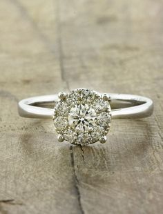 At first glance, this piece looks like one large diamond solitaire. However, upon closer examination you see that one brilliant diamond is surrounded by a halo of slightly smaller diamonds.