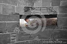 Modern day meets the past as a boy looks into an underground world war 11 bunker built from concrete and bricks.