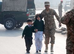 """What happened today is beyond what we could imagine."" (Above: A soldier escorts students from the Army Public School in Peshawar during the attack by Taliban gunmen. Photograph by Khuram Parvez/Reuters)"