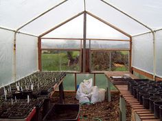 Greenhouse made from old metal carport frame, reclaimed wood and windows, and plexiglass