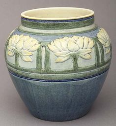 """Newcomb College - Leona Nicholson.  Art Pottery High Glaze Vase. Circa 1906. The shoulder Decorated with a Bold Frieze of Waterlilies in cream and blue set in a green rectilinear framework above a blue body, base Marked with Newcomb Cypher, registration mark """"BK9"""", a """"W"""" indicating a white clay body and Leona Nicholson's Decorator's Mark."""
