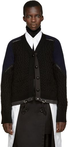 Long sleeve cable knit cardigan in black. Y-neck collar. Button closure at front. Welt pockets at waist. Lace trim at shoulders and sleeves. Navy waffle knit panelling at sleeves. Drawstring at hem with silver-tone stoppers. Tonal stitching.
