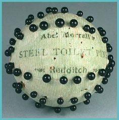 """Antique Abel Morrall Pin Ball  English * Circa 1890-1900  This interesting pinball is one I've never seen before. It is marked """"Abel Morrall's Steel Toilet Pins - Redditch"""". It is stuck with black glass headed toilet pins and most seem to be there. It's made of very heavy cardboard and is in great shape and completely round. It's about 1 1/2"""" in diameter."""