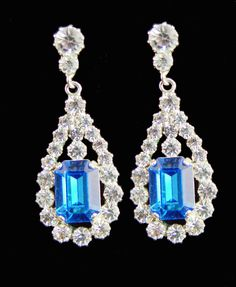 The free swinging square shaped sapphire earrings surrounded with diamonds and hanging from three collet stones match a necklace of oblong sapphires, which were given to Princess Elizabeth by King George as a wedding gift    Our replica earring are made as near as possible to the original pieces.  The earrings are finished in silver plating