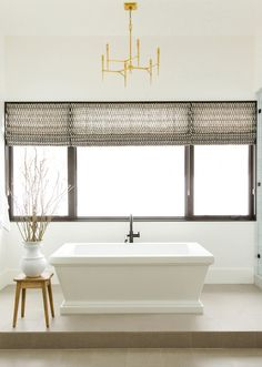 In the master bath, a chandelier by Arteriors hangs above a Kallista tub. Shades in a Clay McLaurin fabric add a touch of pattern.