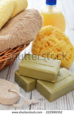 "Greek olive soap with shower gel and bath towels on wooden background The words on soap translates as ""best quality"" - stock photo"