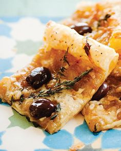 Caramelized Onion & Olive Puff Pastry Tart 1 sheet puff pastry plain flour 4 tablespoons olive oil 5 large onions, peeled and thinly sliced 4 tablespoons water 1 cup Kalamata olives fresh thyme salt & pepper, to taste