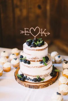 Two-tier naked layered wedding cake with laser cut topper and berries