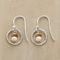 "EVERYWHERE EARRINGS -- Casual or dressy, these earrings shine with hammered sterling circles in which a brass-topped pearl sways sweetly. Sterling silver wires. Exclusive. 3/4""L."