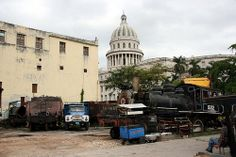 Train graveyard with old locomotives smack in the middle of Havana. The Capitolio can be seen in the background.