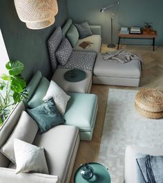 Canapé houssé beige et vert pouvant asseoir cinq personnes et composé de modules d'angle, de modules-siège et de repose-pieds à rangement intégré.