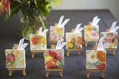 mini canvas + easel as a place card/favor. blick.com sells mini canvases and easels for a total of $3 per place card/favor.