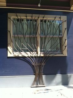 Wrought-iron window bars sculpture. What a great idea/way to hide the ugliness of the standard bars