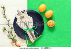 Easter table setting with spring flowers and cutlery. Rustic green table cloth on white wood background. Holidays background with copy space.