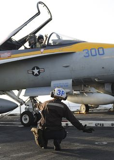 U.S. 5TH FLEET AREA OF RESPONSIBILITY (Sept. 17, 2013) Airman Victoria Cheverdine, on the deck, signals to Lt. Cmdr. Kevin Lyons, both assigned to the Blue Diamonds of Strike Fighter Squadron (VFA) 146, while preparing for flight operations on the flight deck of the aircraft carrier USS Nimitz (CVN 68). Nimitz Strike Group is deployed to the U.S. 5th Fleet AOR conducting maritime security ops and theatre security coop efforts. (U.S. Navy photo by Siobhana R. McEwen/ Released) Us Navy Aircraft, Navy Aircraft Carrier, Military Jets, Military Aircraft, Fighter Aircraft, Fighter Jets, Naval Station Norfolk, Kevin Lyons, Uss Enterprise Cvn 65
