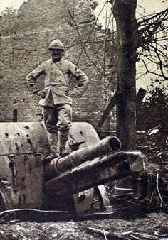 France, 1916. At Herbecourt, Somme, a telephone operator who helped adjust the aim, stands atop a German gun that he helped spot.