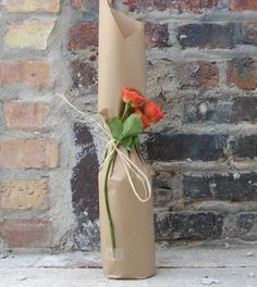 Gift wrapped wine. Simple but elegant. Plain kraft paper and a beautiful orange rose as a contrast colour.