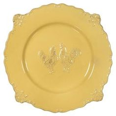 "Add a farmhouse-chic touch to your tablescape with this delightful ceramic plate, featuring an embossed chicken motif and scrolling scalloped edges.  Product: Dinner plateConstruction Material: CeramicColor: Antique yellowFeatures: Scrolling scalloped edgesDimensions: 2"" H x 12"" Diameter"