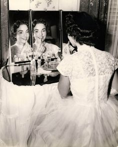 A 1950s bride finishing up her makeup before the ceremony.