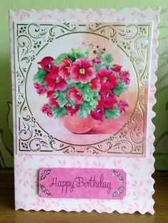 This is a pastel pink printed card with a deckled edge It has a beautiful square pink /gold foiled topper with a circular image of pink pansies in a vase.  It has a pink message plate which reads Happy Birthday.  It has an envelope and is in a clear bag. It is blank inside for your message.I can add a name etc if you wish.1