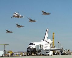 Space Shuttle Endeavour on runway receives a high-flying salute from its sister shuttle